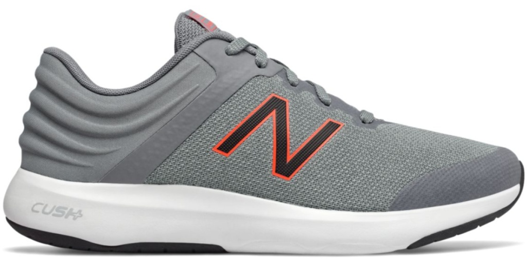 greay shoes with a black and orange New Balance logo on side with white sole with cush wording on back side of heel