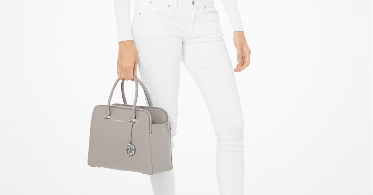 woman holding michael kors leather satchel