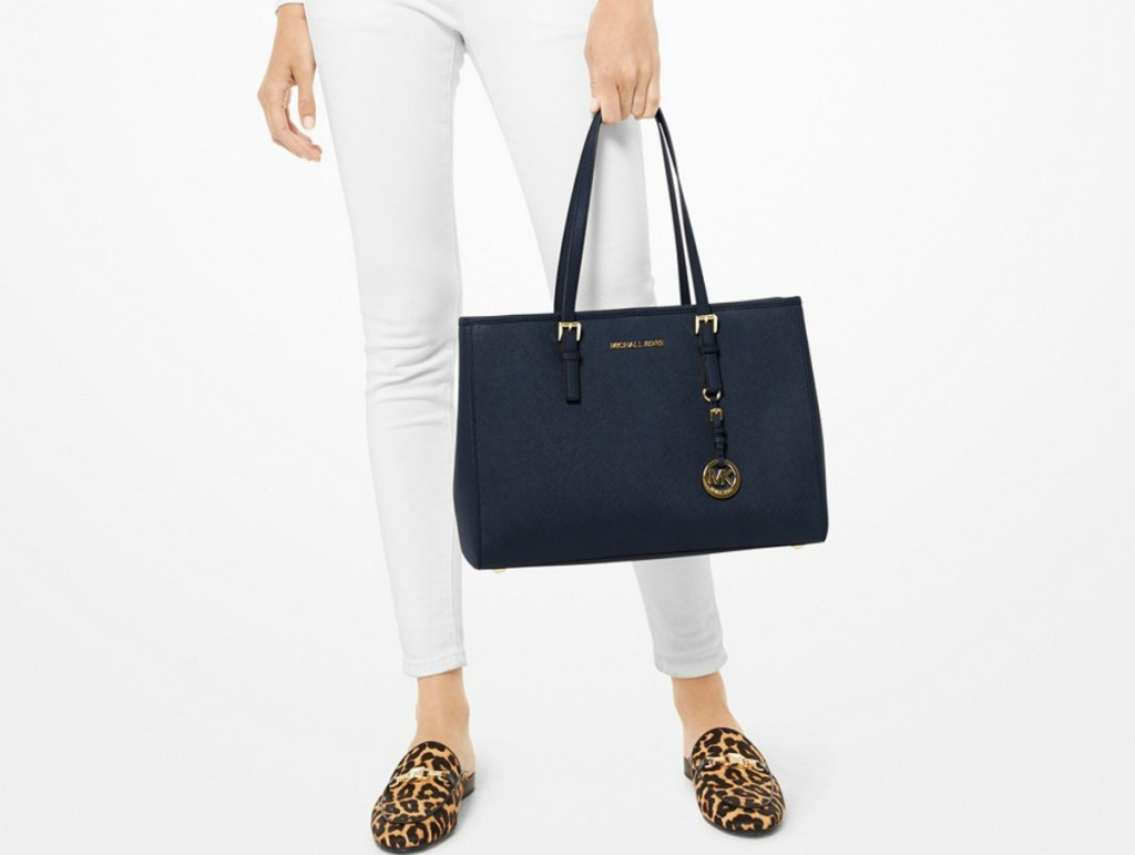 woman holding Michael Kors Jet Set Large East West Tote in blue