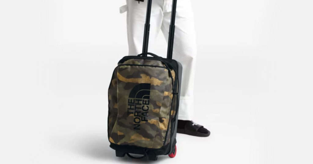 man holding north face duffel bag