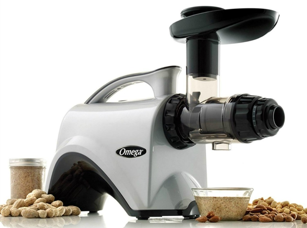 Omega nutrition extractor and juicer surrounded by nuts and nut butter