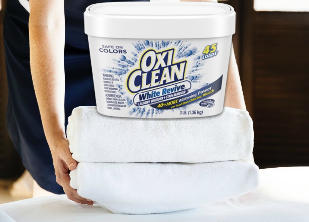Woman stacking two folded towels with a tub of OxiClean on top