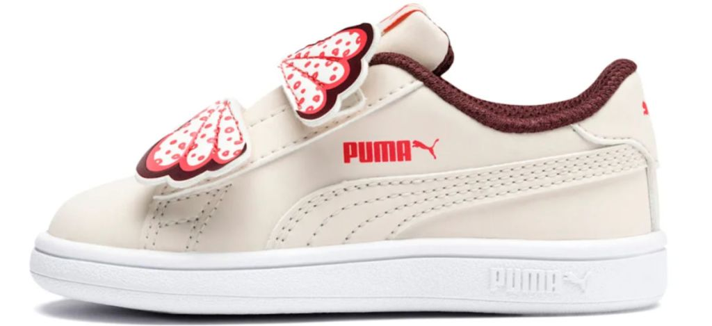 gold puma shoe with butterfly closure and puma logo on side with white sole