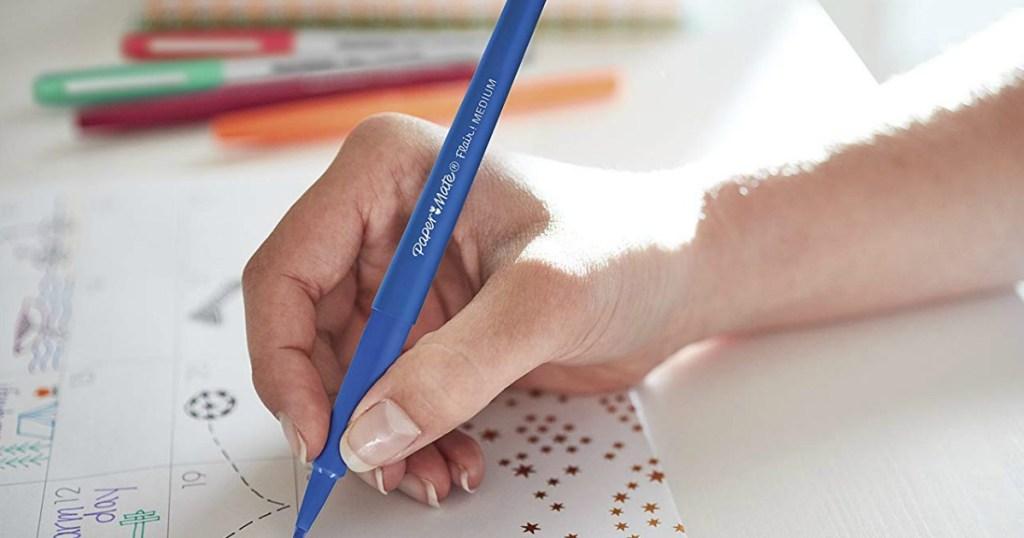 hand using a felt tip pen to write