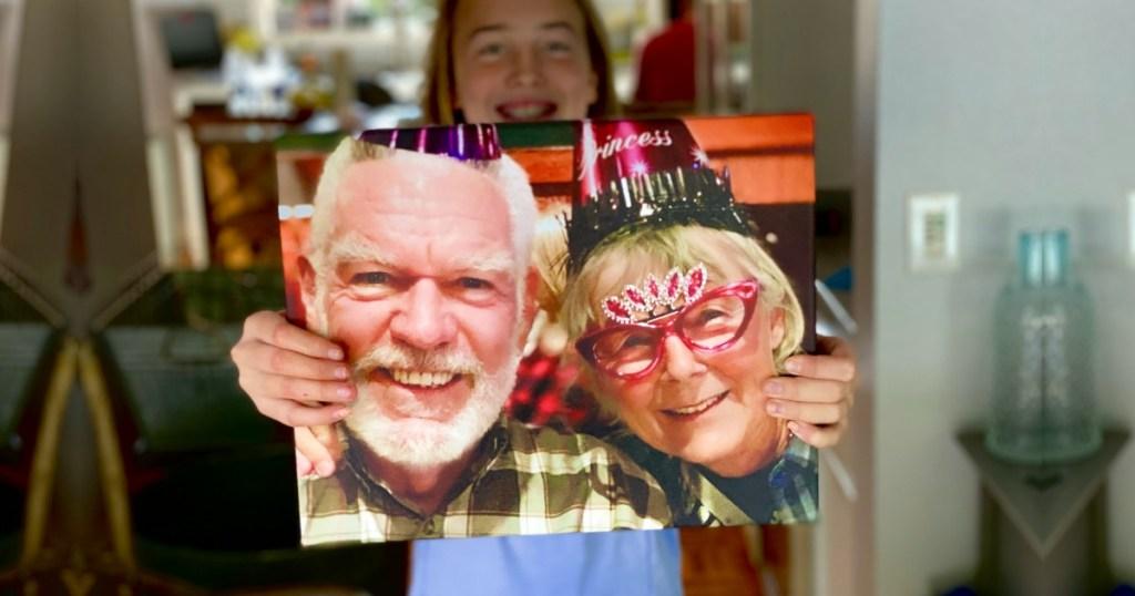 girl holding photo canvas of granpa and grandma