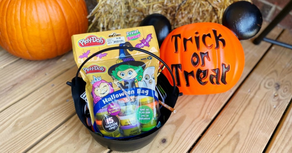 Play-Doh Halloween bag in trick or treat bucket next to Halloween decor on porch