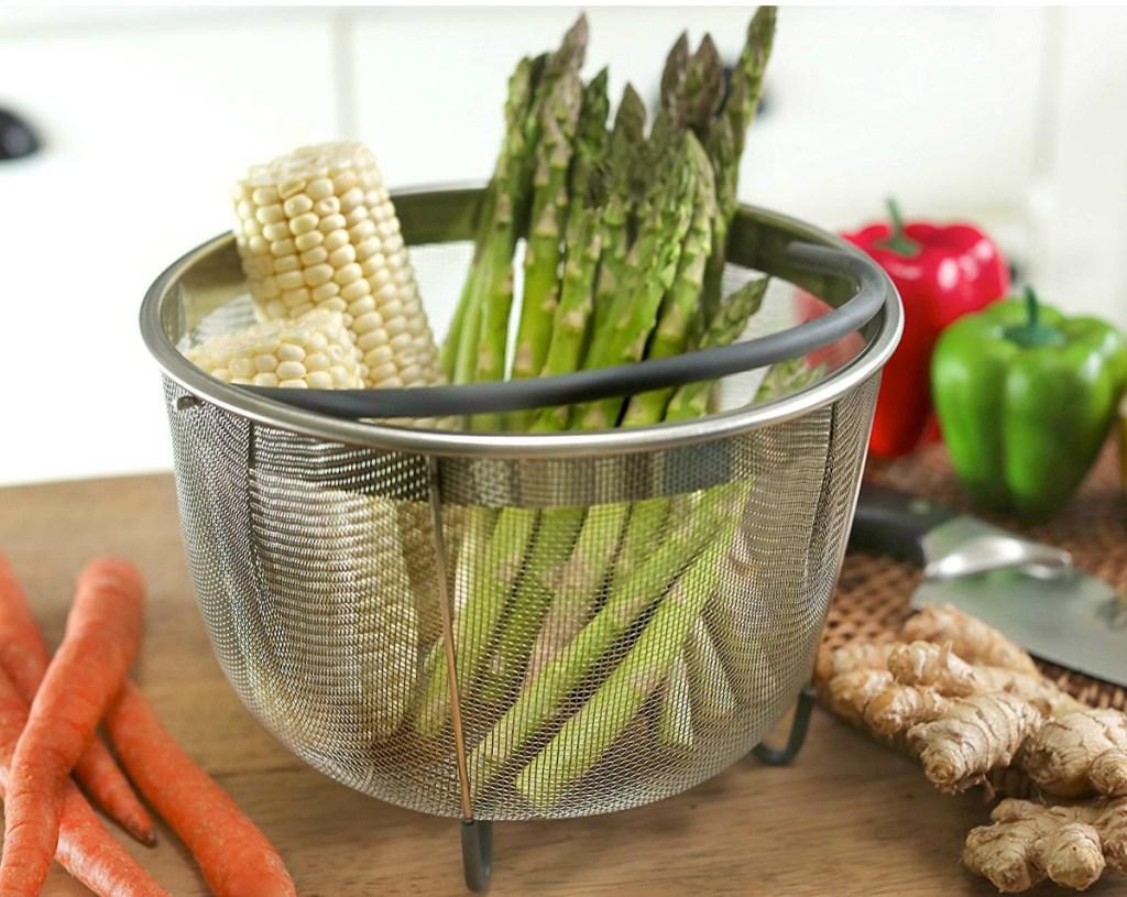 Pressure cooker steamer basket with corn and asparagus inside