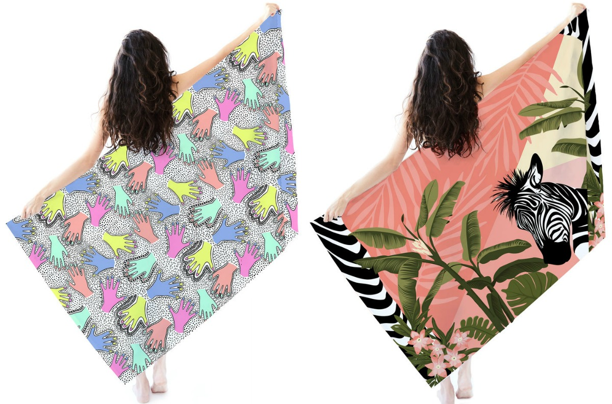Woman holding up two printed beach towels - zebra and hands
