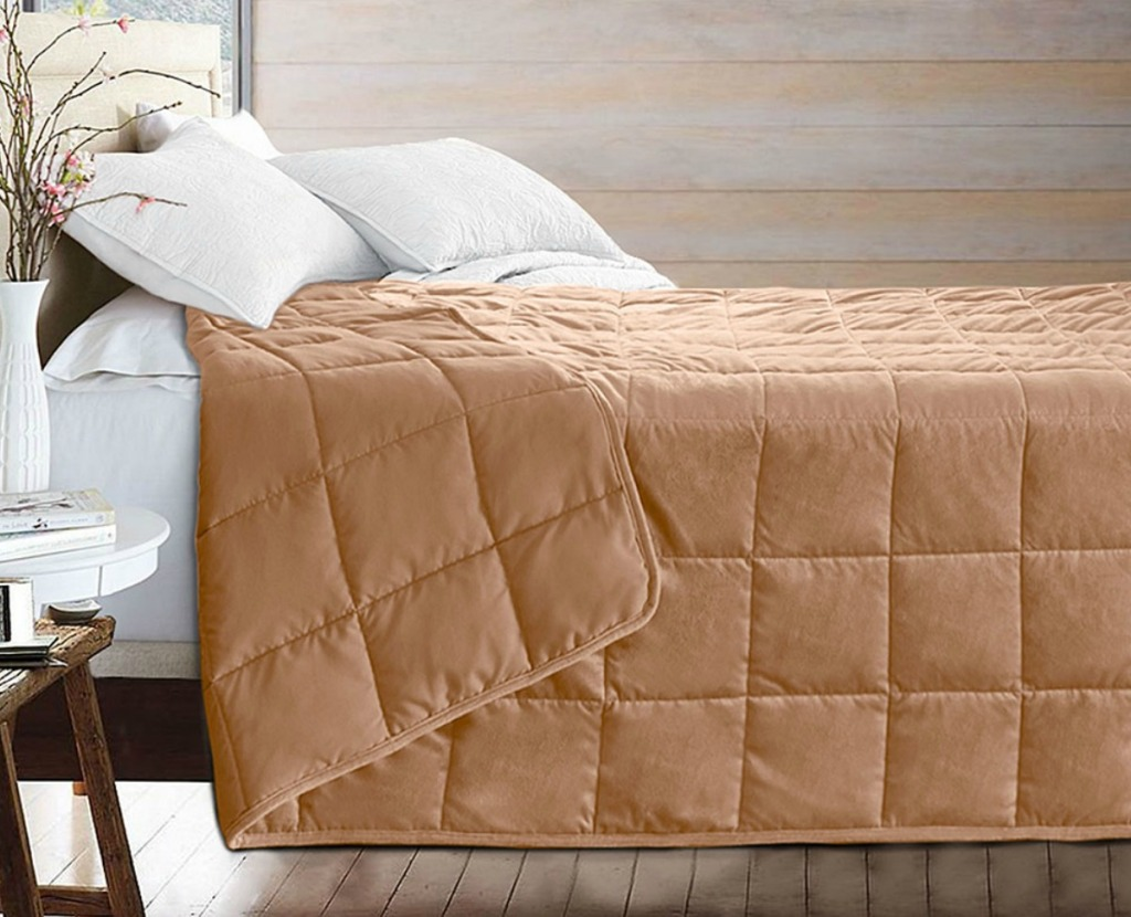 Puredown brand weighted blanket in khaki color on bedspread