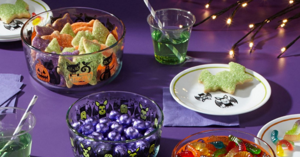 Pyrex Halloween containers on table with purple tablecloth and other Halloween decor