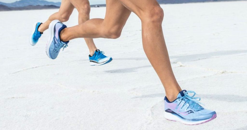 people running on sand in Saucony Shoes