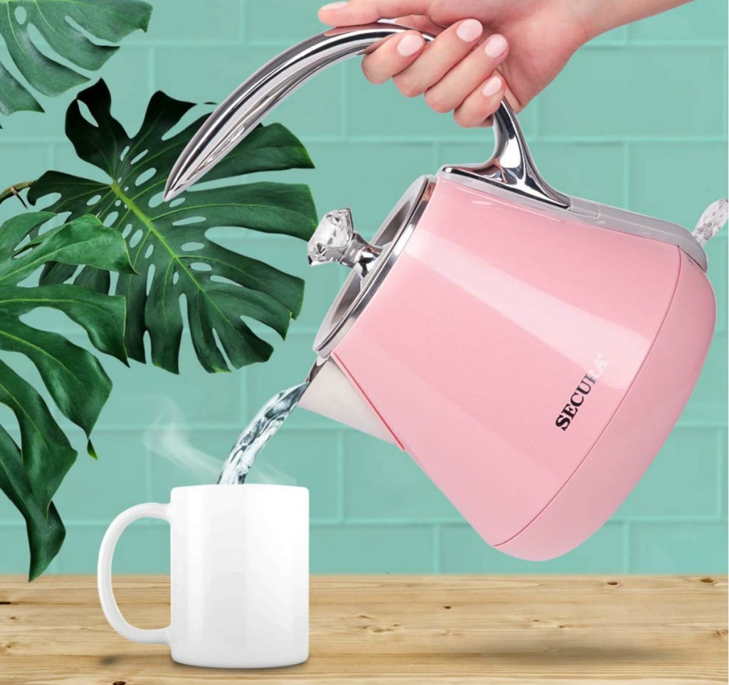 Pink Secura stainless steel electric tea kettle in hand, pouring, near palm leaves