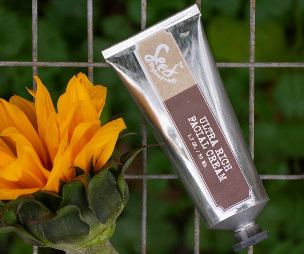 Seed Phytonutrients Ultra Rich Facial Cream in tube on tiled background near flower