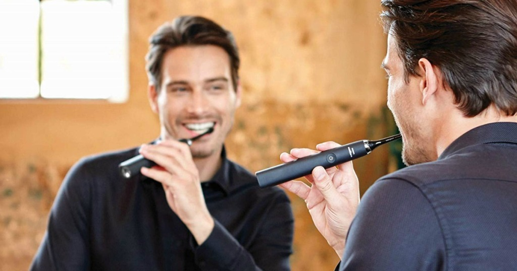 man brushing with black Sonicare DiamondClean Toothbrush in bathroom