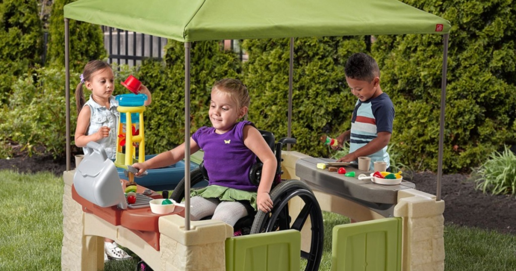 kids playing with step2 patio playhouse
