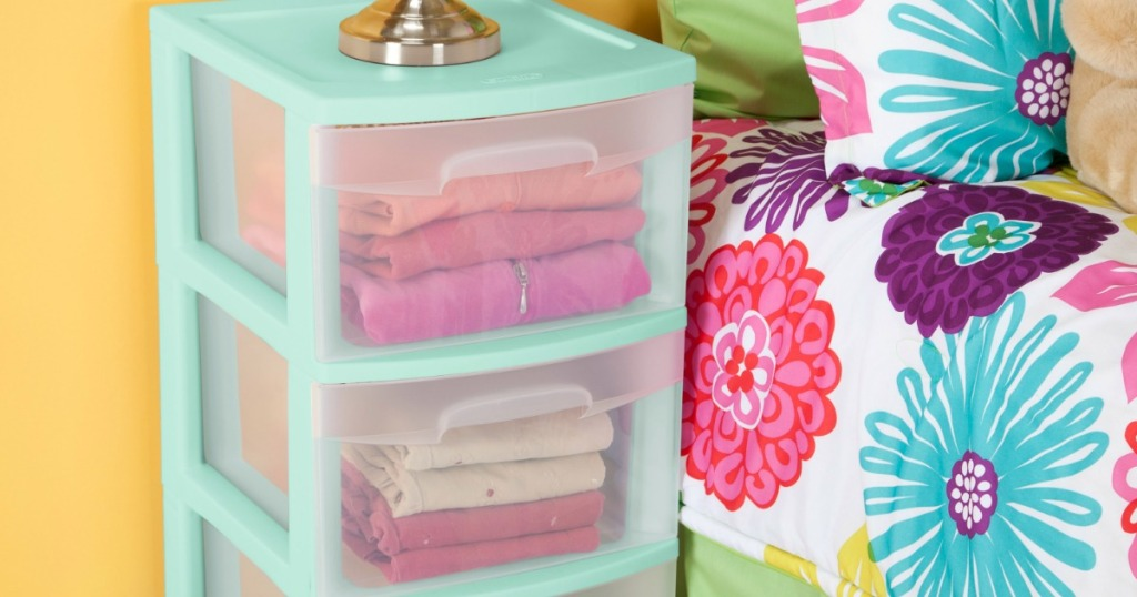 Sterilite storage cart in mint green next to bed