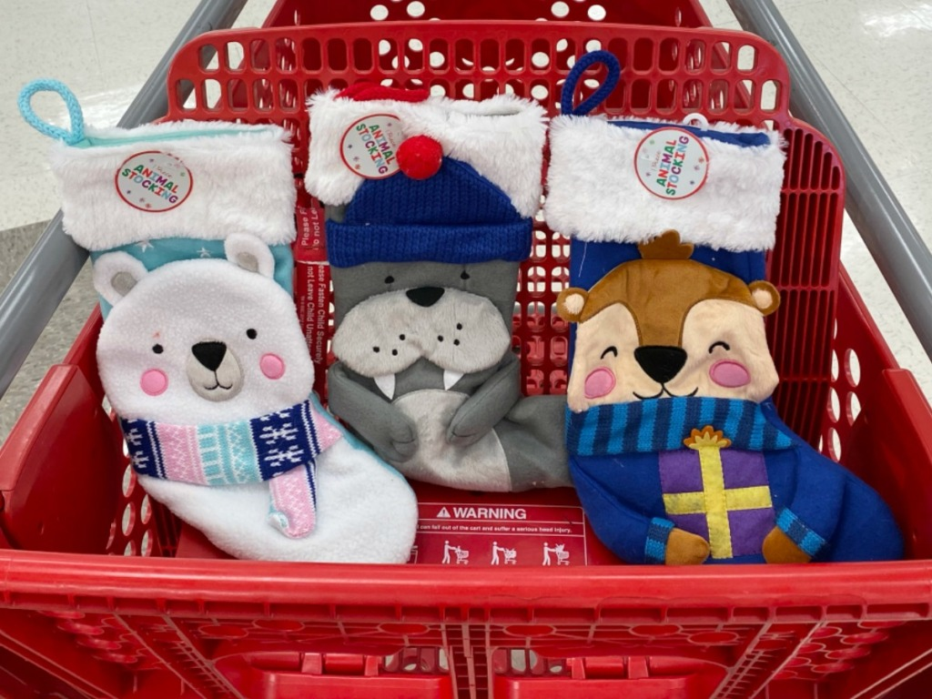 Three animal themed holiday stockings in red Target cart, in-store