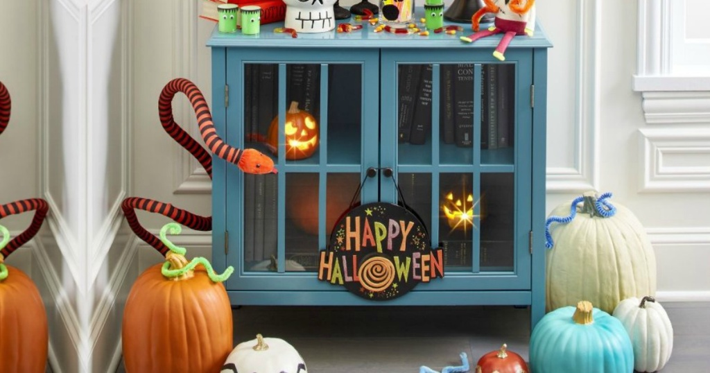 teal cabinet with Halloween decorations in and around it