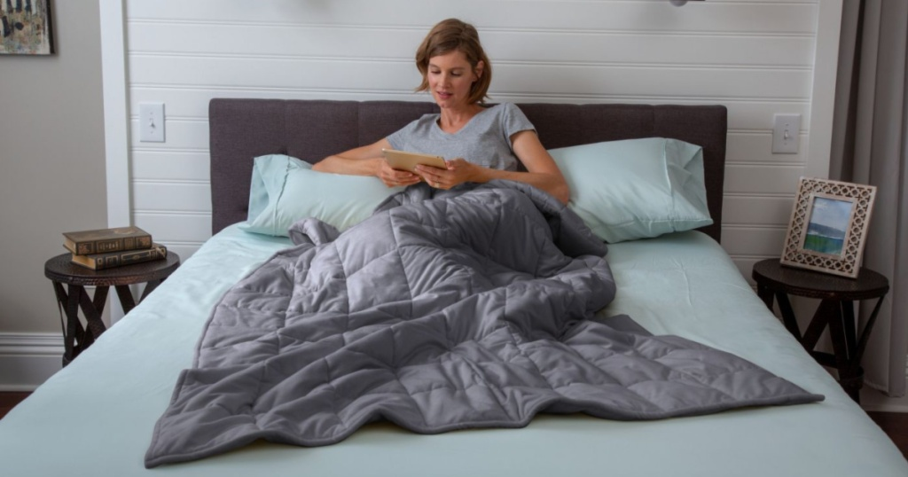woman using gray tranquility weighted blanket on bed