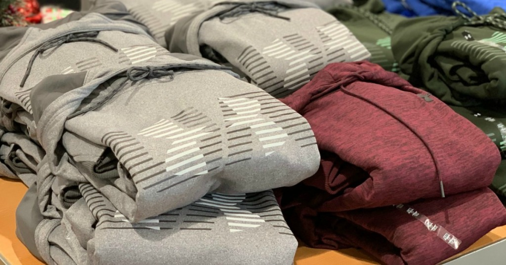 Men's UA Hoodies folded and stacked on display at Dick's Sporting Goods