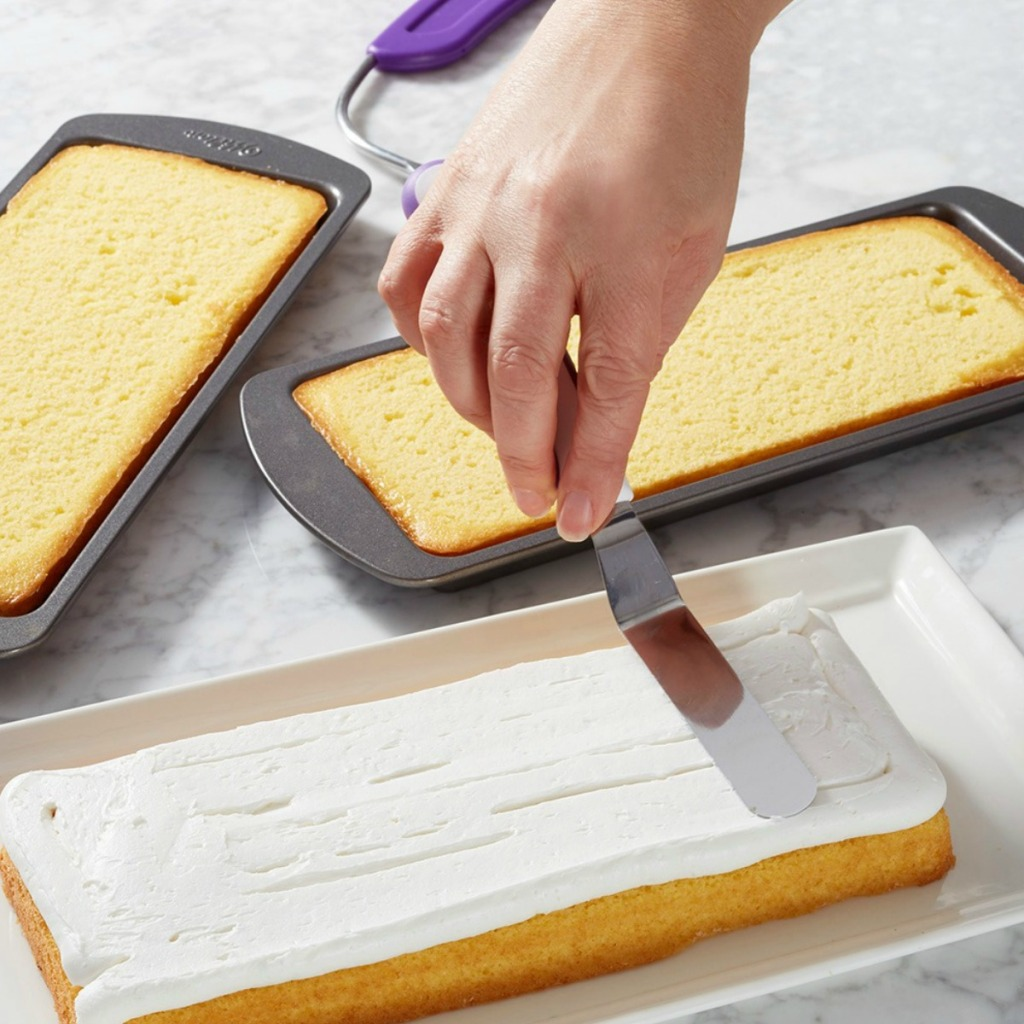 Woman frosting layer of sheet cake