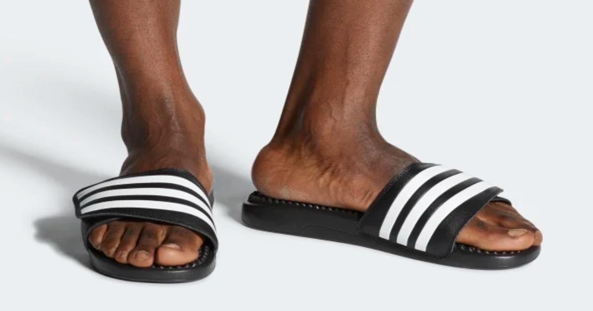Men's feet wearing Adidas Slides