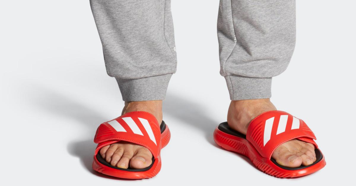 man wearing adidas slides