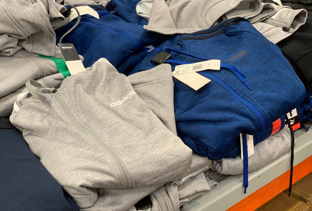 piles of gray and blue adidas track jackets hoodies