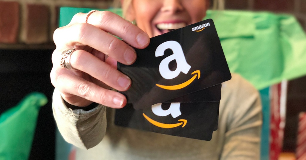 woman holding up Amazon gift cards