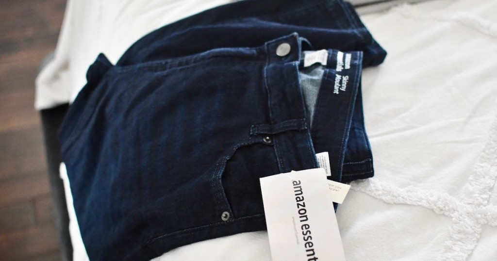 dark wash jeans laying on bed with amazon essentials tag
