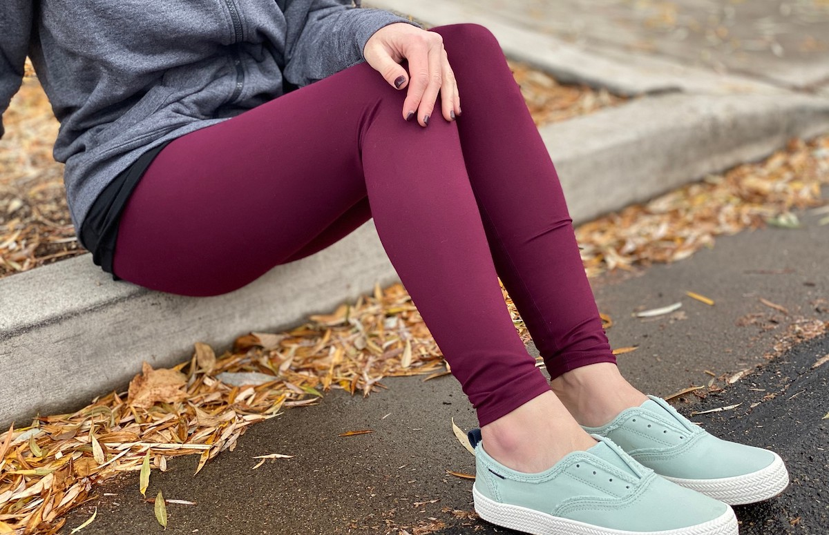 woman wearing purple leggings with blue shoes outside with leaves