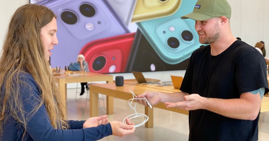 man and apple store employee exchanging phone chargers