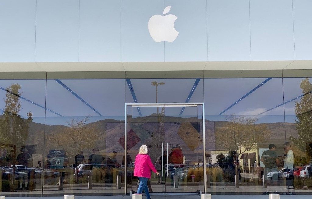 woman walking into apple store front outside