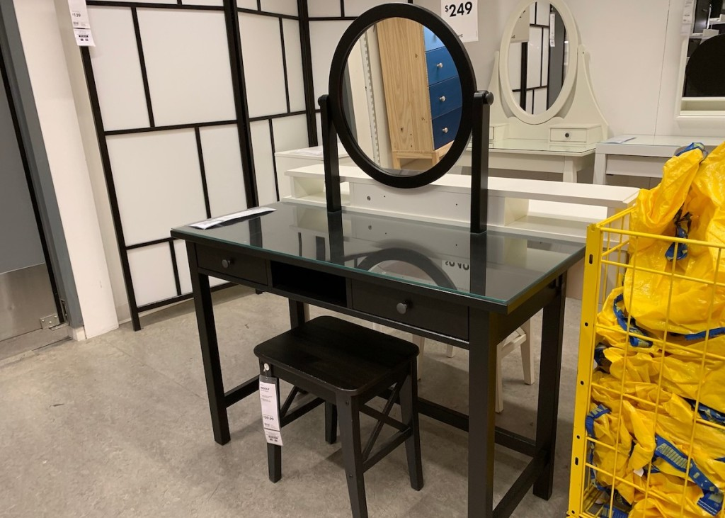 black makeup vanity with round mirror and stool in IKEA store
