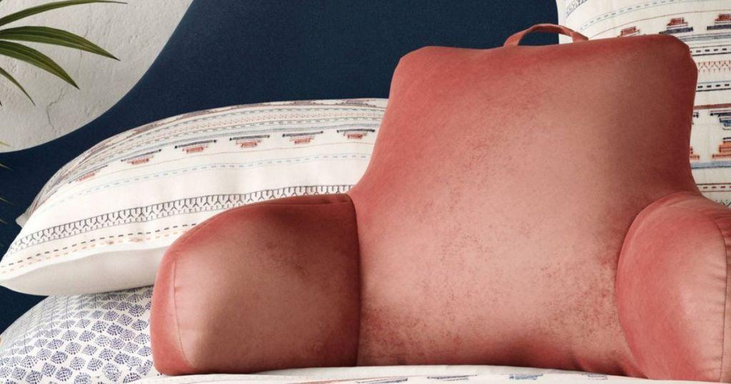 orange backrest pillow on bed