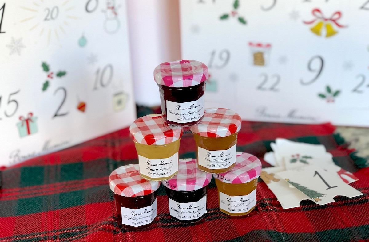 stack of mini jelly jars on christmas towel with advent calendar in background