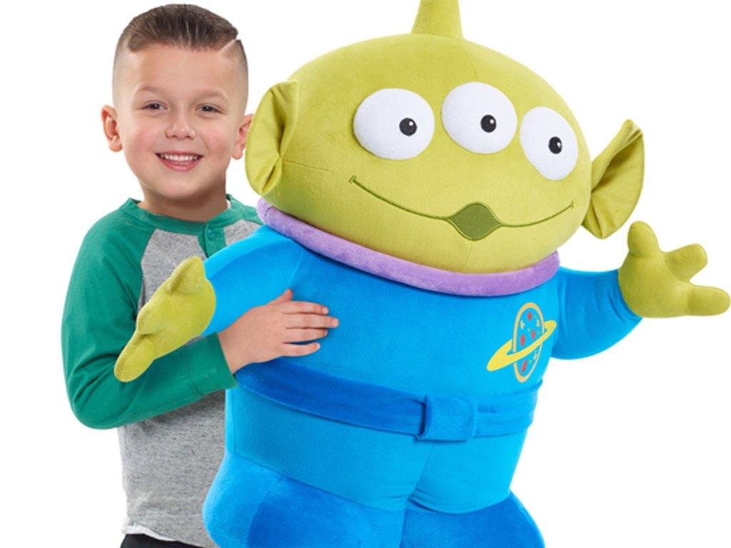 little boy holding a gigantic plush of toy story 4 alien