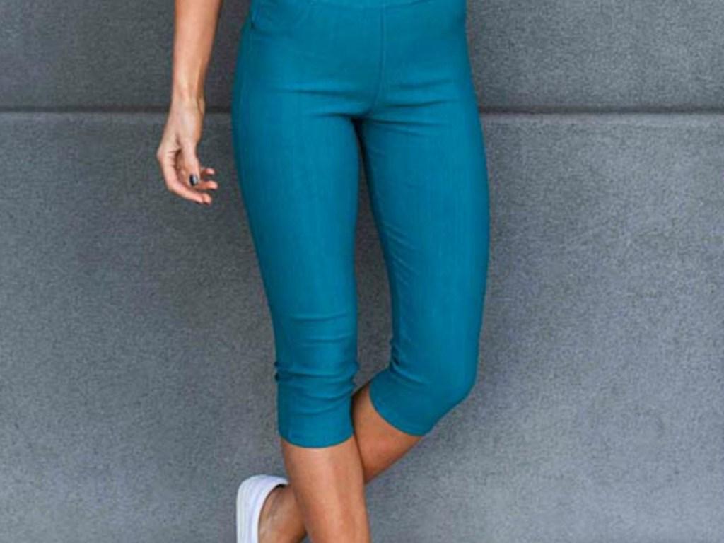 woman wearing pair of teal pants on sidewalk