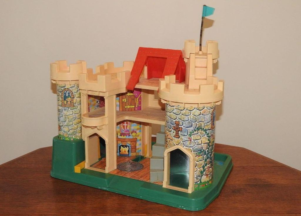 vintage fisher price castle sitting on wood table