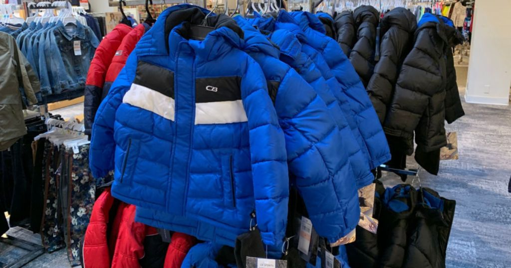 blue and white and black puffer jacket hanging in store
