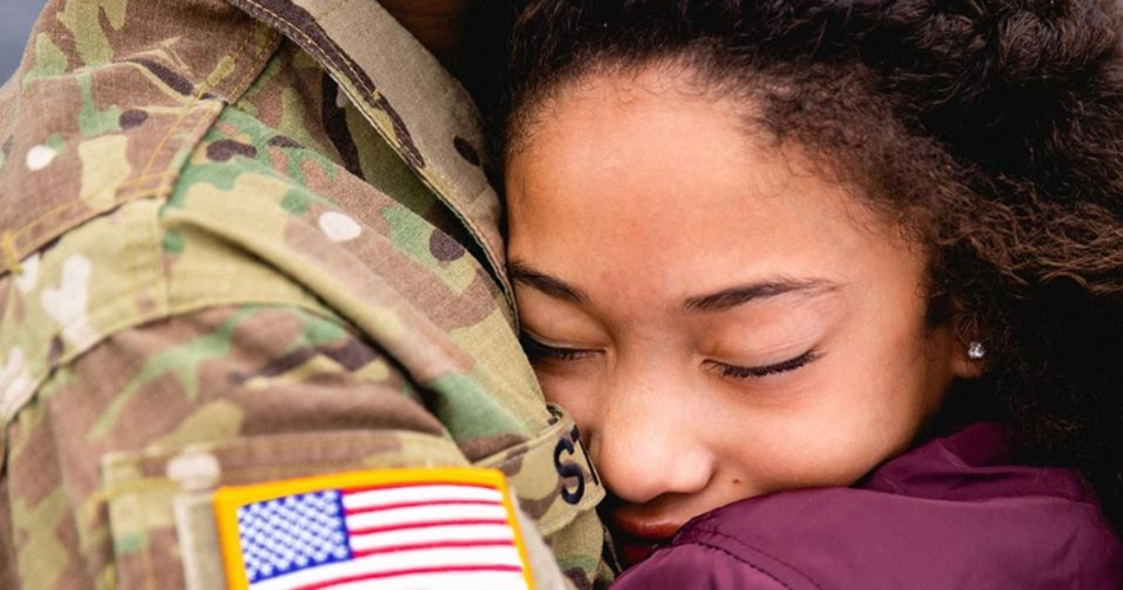 Girl hugging military personnel