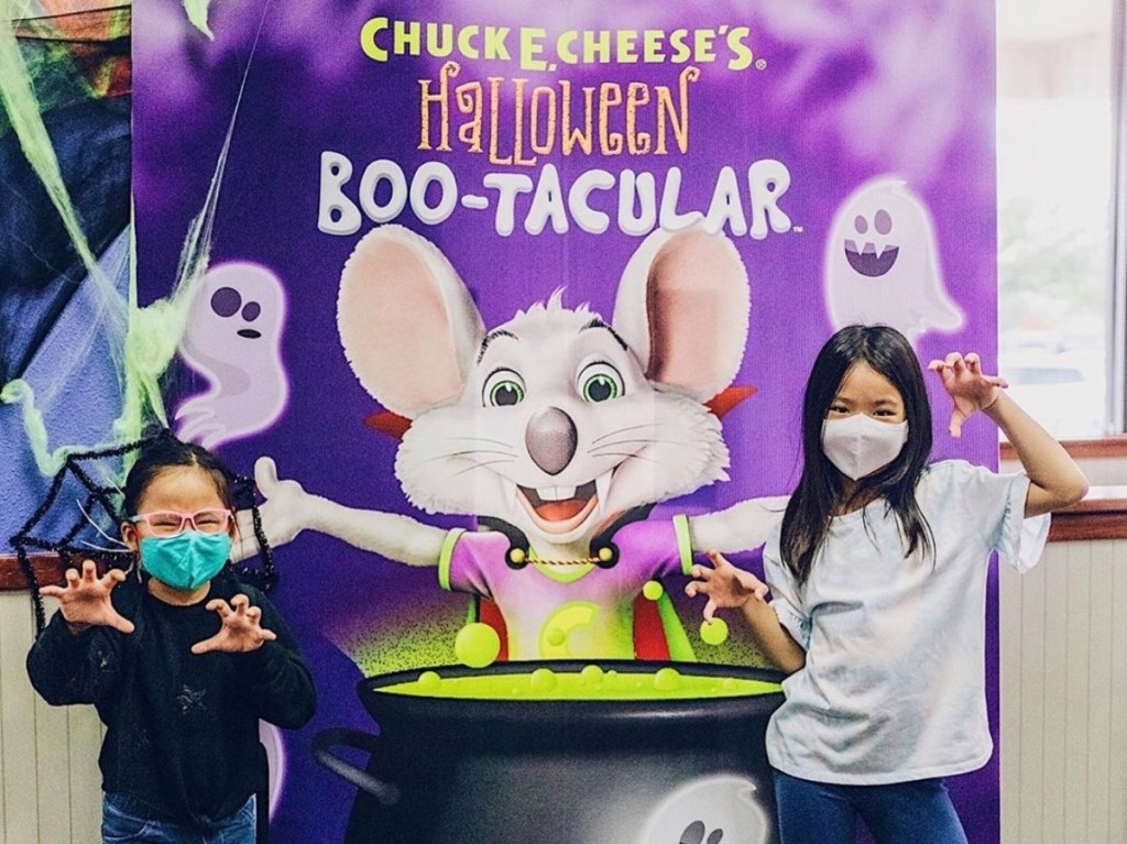 girls standing in front of Chuck E Cheese cauldron