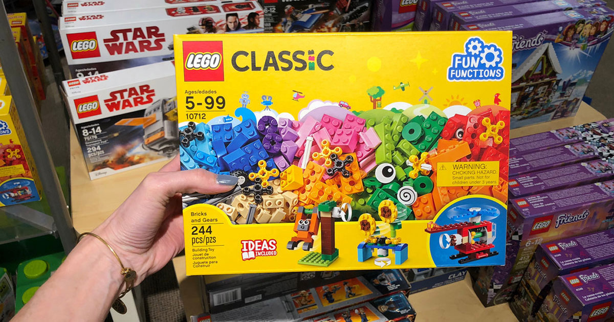 hand holding LEGO classic bricks and gear