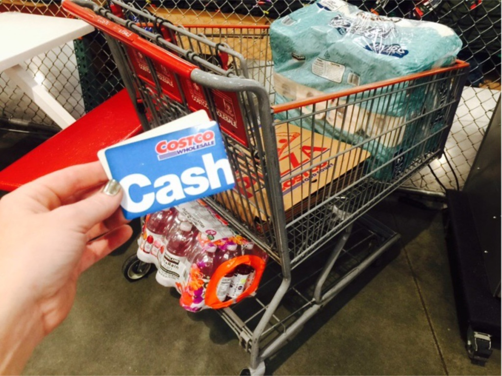 hand holding costco cash card in front of grocery cart