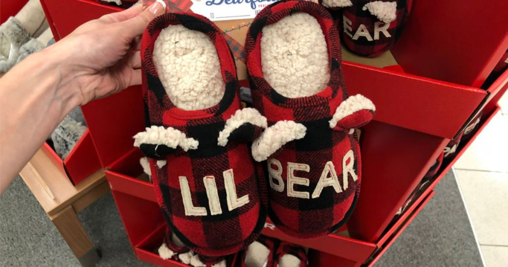 hand holding lil bear slippers in store