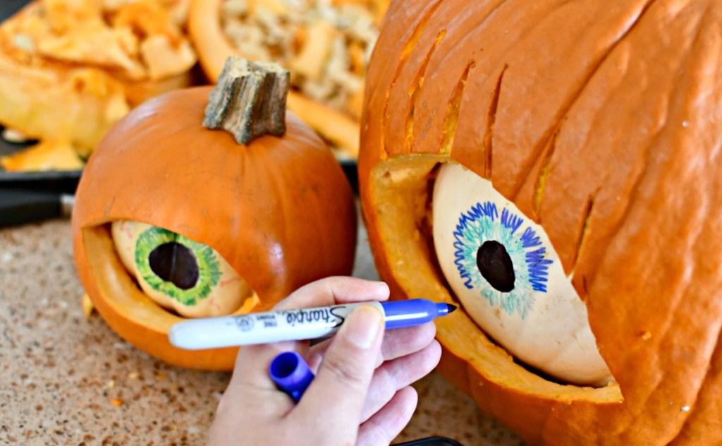 drawing eye details on a white pumpkin