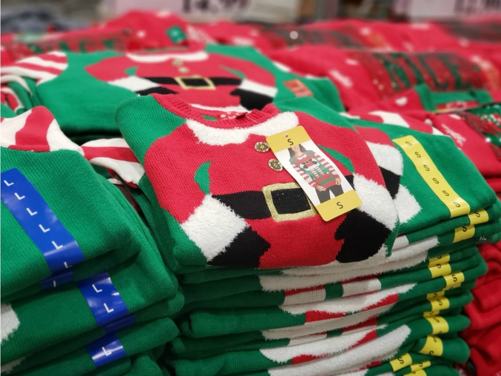 pile of Christmas sweaters on display in store