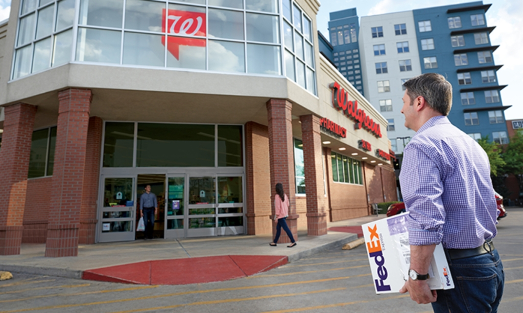 Man carring FedEx package into Walgreens