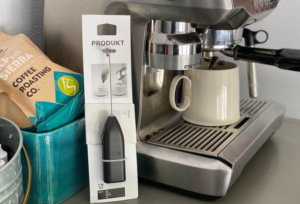 IKEA milk frother sitting next to coffee machine with mug