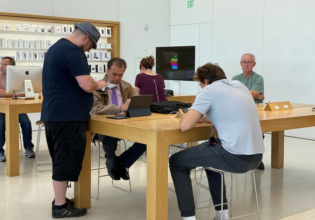 people standing at genius bar at apple store